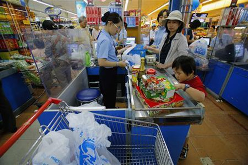 Customers check out at a super market in Ho Chi Minh city.