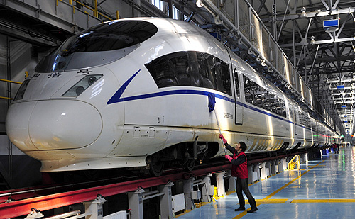A worker cleans a CRH380B high-speed Harmony bullet train as it stops for an examination during a test run, at a bullet train exam and repair center in Shenyang, Liaoning province.