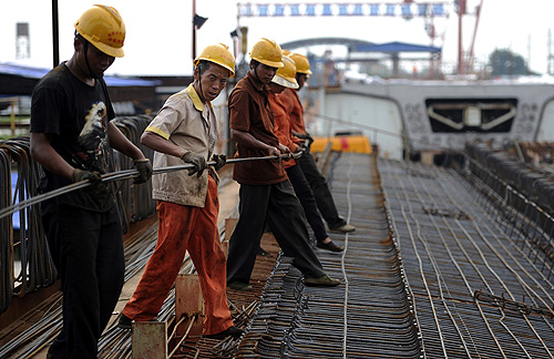 Labourers place steel reinforcement bars atop an unfinished steel box girder for a high-speed railway viaduct in Hefei, Anhui province.
