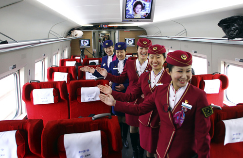 Attendants pose for pictures inside a high-speed train during an organized experience trip from Beijing to Zhengzhou, as part of a new rail line.