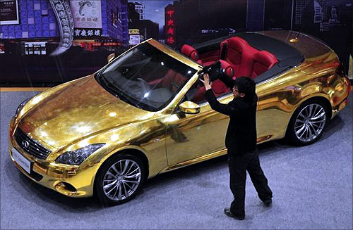 A man films a gold-plated Infiniti G37 at a jewellery store in Nanjing, Jiangsu province.