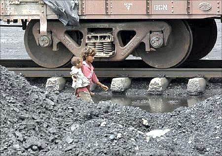 Children of labourers walk beside a railway track inside a coal yard on the outskirts of Ahmedabad.