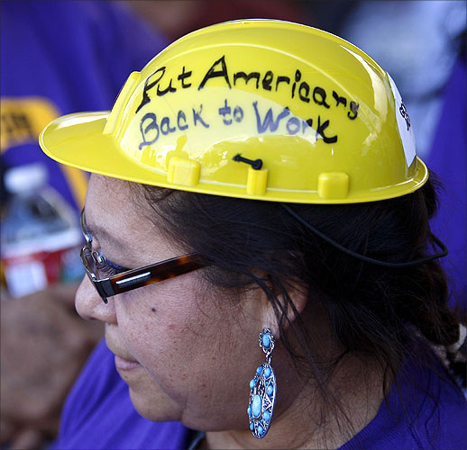 Protester Victoria Marquez wears a hard hat with the message to put Americans back to work.