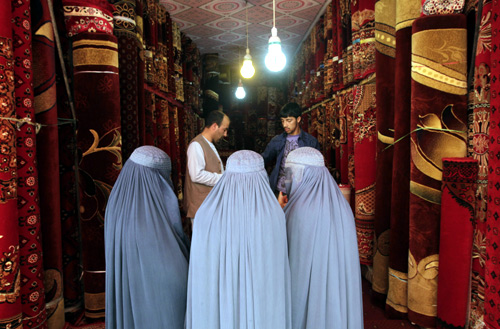 Afghan women talk to a carpet vendor in his shop in Kabul.
