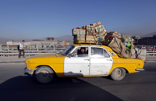 A Russian-made taxi loaded with boxes of vegetables and fruits drives down the road  in Kabul city.