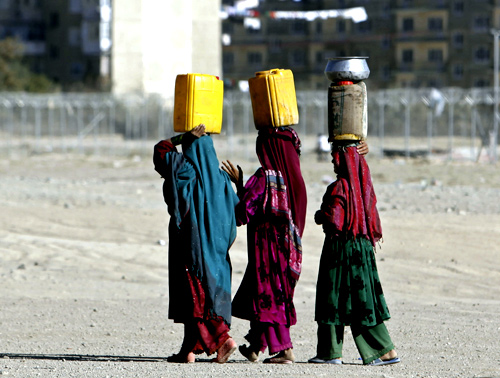 Afghan internal displaced refugee women carry water on their head near their shelter at the outskirts of Kabul.