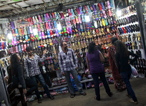 People shop for shoes at a roadside store at a market.