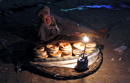 An Afghan man sells bread along a street as he waits for customers at the old part of Kabul.