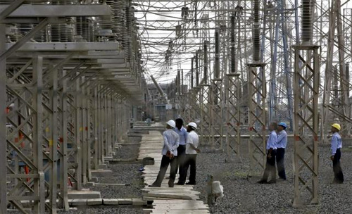 Engineers inspect electric transmission lines at Adani Power Company thermal power plant at Mundra in Gujarat.