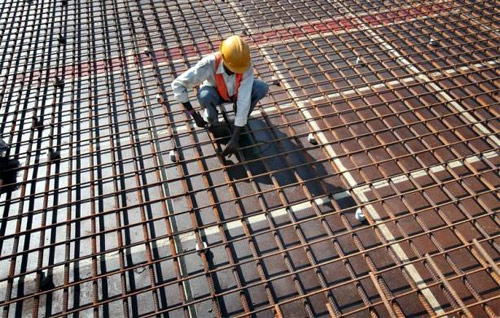 A worker fastens iron rods together at the construction site of a bridge on Srinagar-Jammu national highway in the outskirts of Jammu.