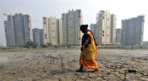 A woman labourer walks past a residential estate under construction in Kolkata.