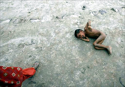A girl lies on the ground as she cries for food in Akhera village in Haryana.