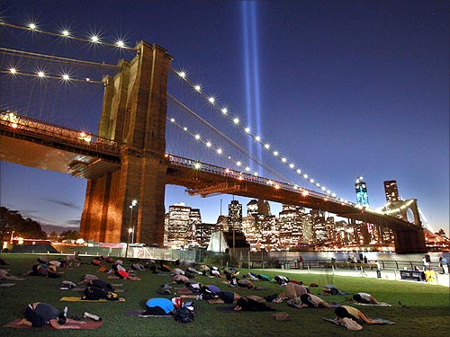 People take part in a sunset yoga session as the Tribute in Light shines over the Brooklyn Bridge.