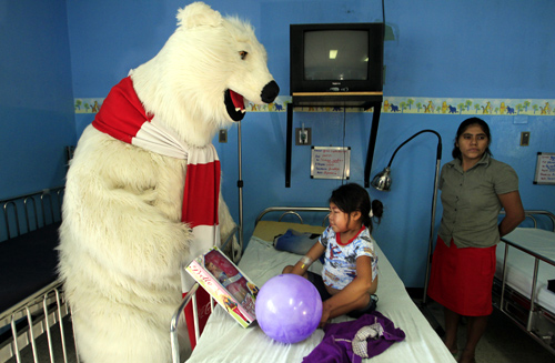 A Coca-Cola polar bear mascot visits a patient at a children's hospital in Managua.