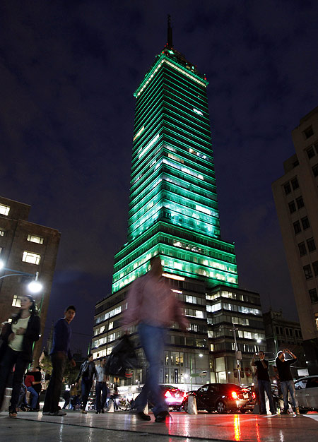 Pedestrians walk past the Torre Latinoamericana illuminated by LED lights, as part of an artistic intervention, in downtown Mexico City.