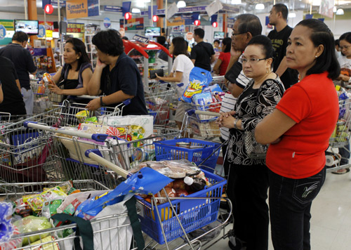 People queue to pay for groceries at a supermarket in Paranaque, Metro Manila.