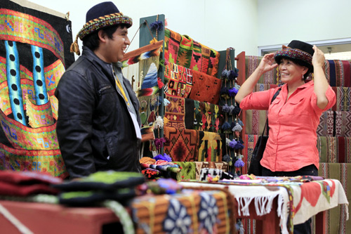 A customer tries a traditional hat made by an Andean man during the