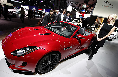 A model stands next to a Jaguar F Type S convertible model, winner of the 2013 World Car Awards World Car Design of the Year during a press preview at the 2013 New York International Auto Show in New York.