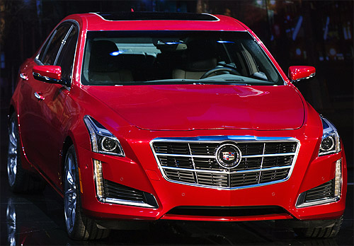 A 2014 Cadillac CTS sedan is displayed on stage during an unveiling ceremony in New York.