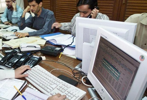 Traders monitor their stocks on computer monitors at the Karachi Stock Exchange.
