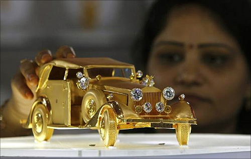 A woman looks at a Rolls Royce RRR65 car model made from pure gold weighing 1.5 kg, displayed at the Gem and Jewellery India International Exhibition 2013 (GJIIE) in Chennai.