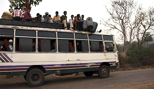 Tribal villagers sit atop of a bus as they travel through the remote district of Kandhamal in Orissa.