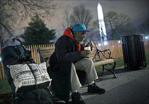 A homeless man sits on a bench with a cup of chili that he received from the Salvation Army in Washington.