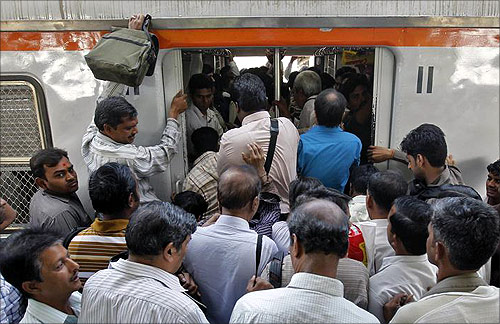 Commuters try to get in an overcrowded train on a railway platform in Mumbai.