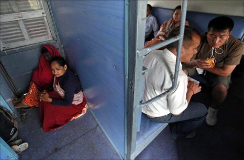 Women sit next to a door as men eat snacks inside the sleeper class compartment of the Kalka Mail passenger train.