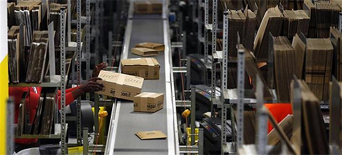 A worker packs boxes at Amazon's logistics centre in Graben near Augsburg.
