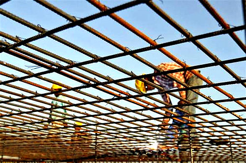 A worker welds iron rods at the construction site of a commercial complex in Ahmedabad.