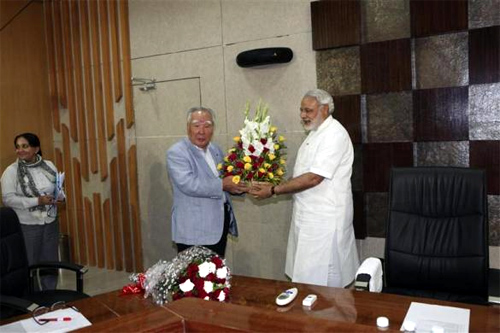 Suzuki Chairman and CEO Osamu Suzuki receives a bouquet from Narendra Modi (R), chief minister of Gujarat.