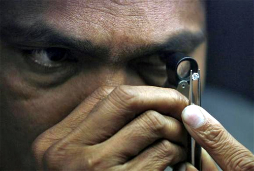 A supervisor checks the shape of a polished diamond inside the diamond processing unit at Surat, in Gujarat.