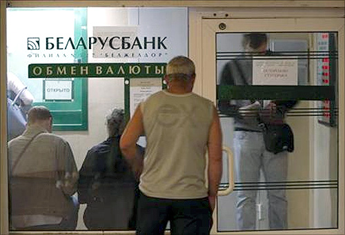 People wait to buy foreign currency inside an exchange office of the Belarus bank in Minsk.