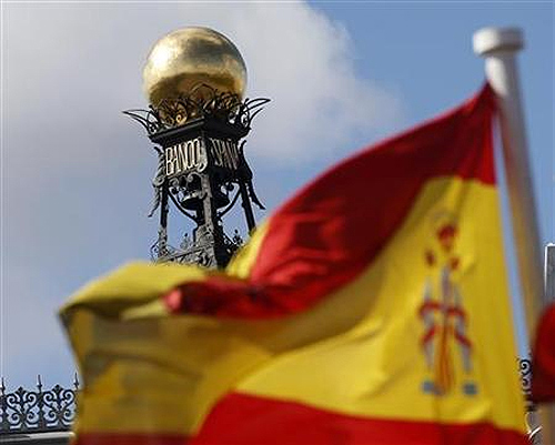 A Spanish flag flutters in the wind in front of the dome of Bank of Spain headquarters in central Madrid.
