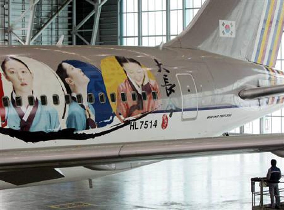 A South Korean looks around the Asiana Airlines plane that had been wrapped with images of heroine Lee Young-ae in Inchon, west of Seoul.