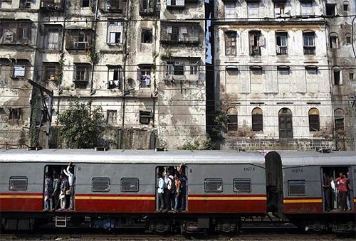 Commuters stand at the open doorways of a suburban train as they head toward their destination in Mumbai.