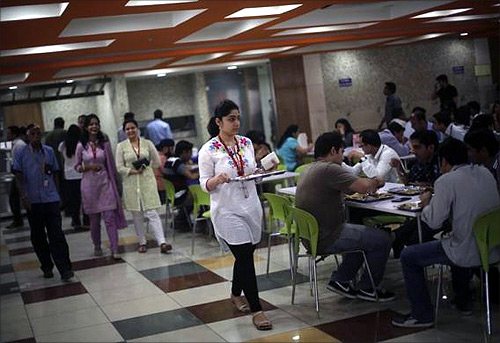 An employee carries her lunch at a cafeteria inside Tech Mahindra office building in Noida on the outskirts of New Delhi.