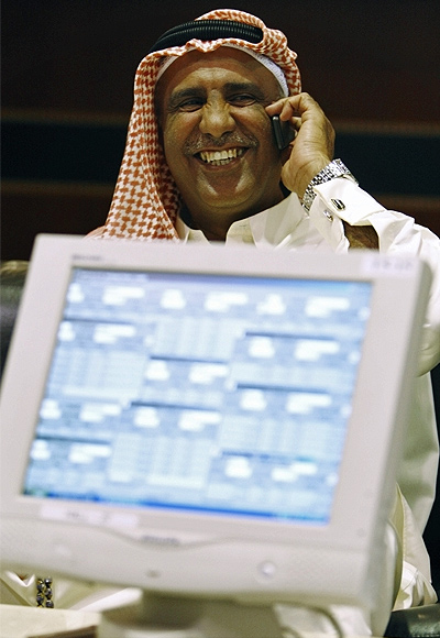 A trader speaks on the phone as he monitors stocks at the Dubai Stock Exchange in the Dubai World Trade Center.