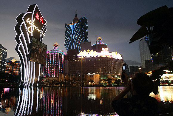 A man takes pictures of hotels and casinos with his mobile phone in Macau.
