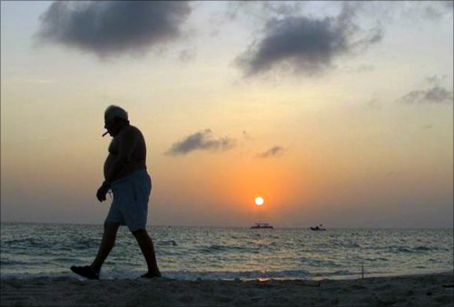 A man smokes a cigar as he walks along Seven Mile Beach in George Town, Cayman Islands.