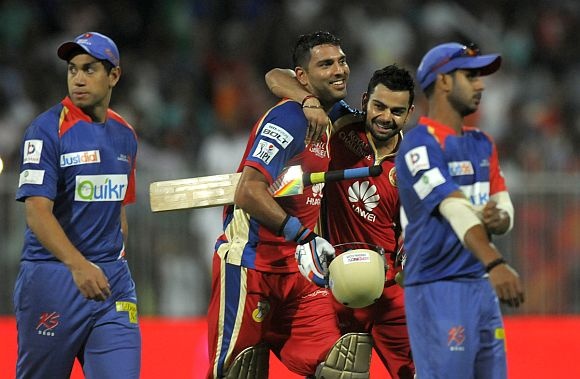Yuvraj Singh and Virat Kohli walk back to the pavillion after winning the game for RCB