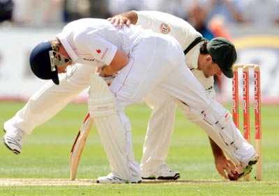 England's Paul Collingwood stops the ball hitting the stumps with his boot as Australia's Ricky Ponting picks it up during their first Ashes Test in Cardiff