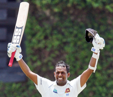 Sri Lanka's Thilan Samaraweera raises his bat and helmet to celebrate scoring his century against India