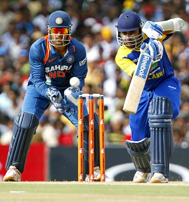 Mahela Jayawardene plays a shot as Mahendra Singh Dhoni watches