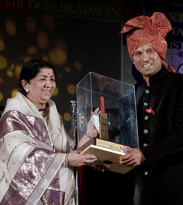 Bollywood singer Lata Mangeshkar presentsSachin Tendulkar with a golden bat during a felicitation ceremony in Mumbai