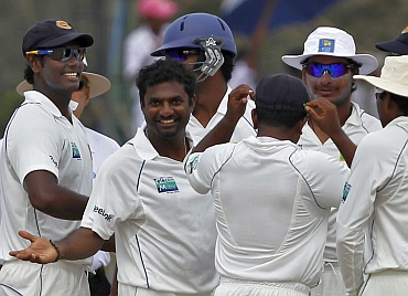 Muttiah Muralitharan celebrates with team-mates after picking Harbhajan Singh