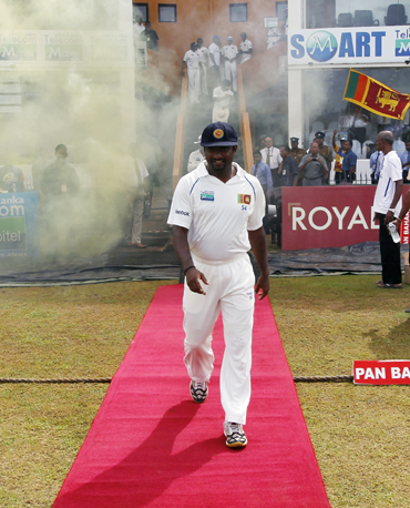 Muralitharan walks to the field on the fifth day of the first Test