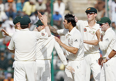 Mitchell Johnson celebrates with teammates after dismissing Murali Vijay
