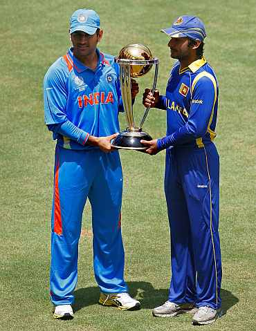 MS Dhoni and Kumar Sangakkara pose with the World Cup trophy at Wankhede Stadium
